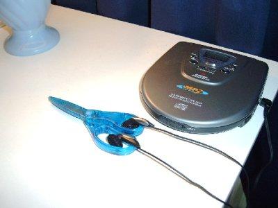 Ohrknöpfe eines mobilen CD-Spielers ruhen in den Griffen einer blauen Kinderschere